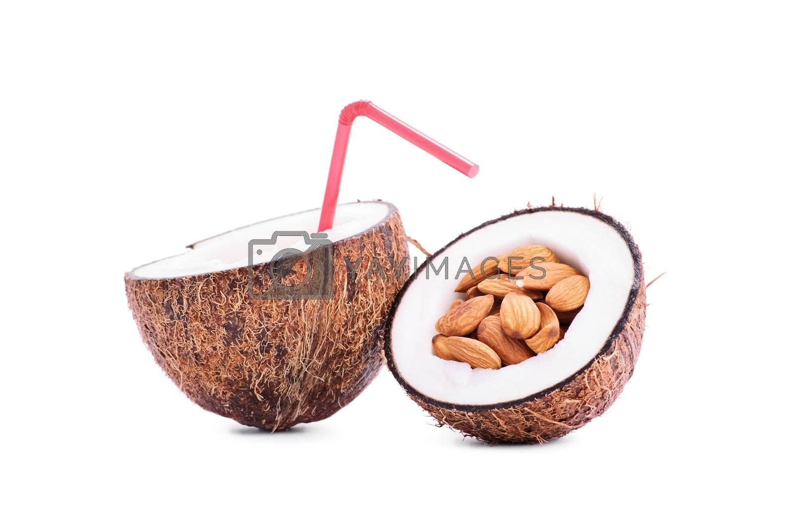 Sliced coconut fruit filled with almonds and coconut milk with a straw, isolated on white background.