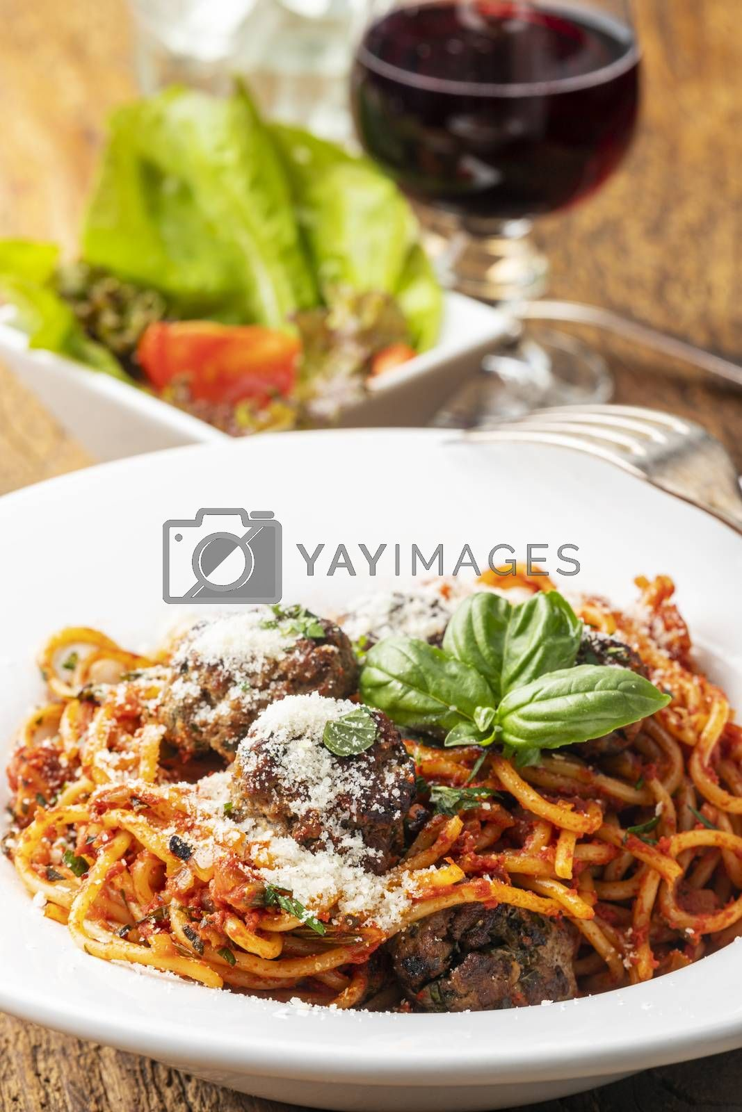 spaghetti with meat balls on dark wood