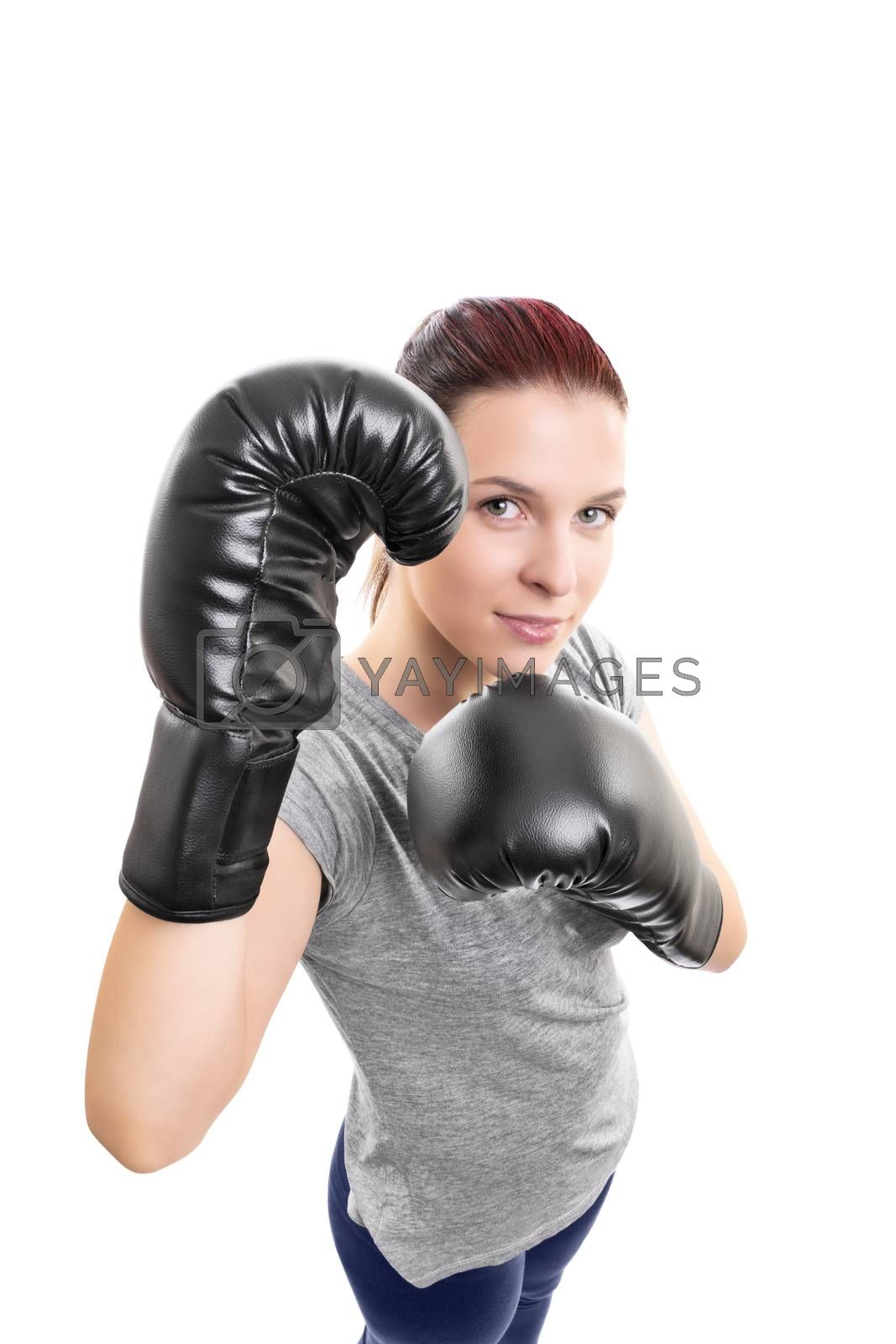 Top down portrait of a beautiful young woman with boxing gloves in a stance with raised arms looking up, isolated on white background.