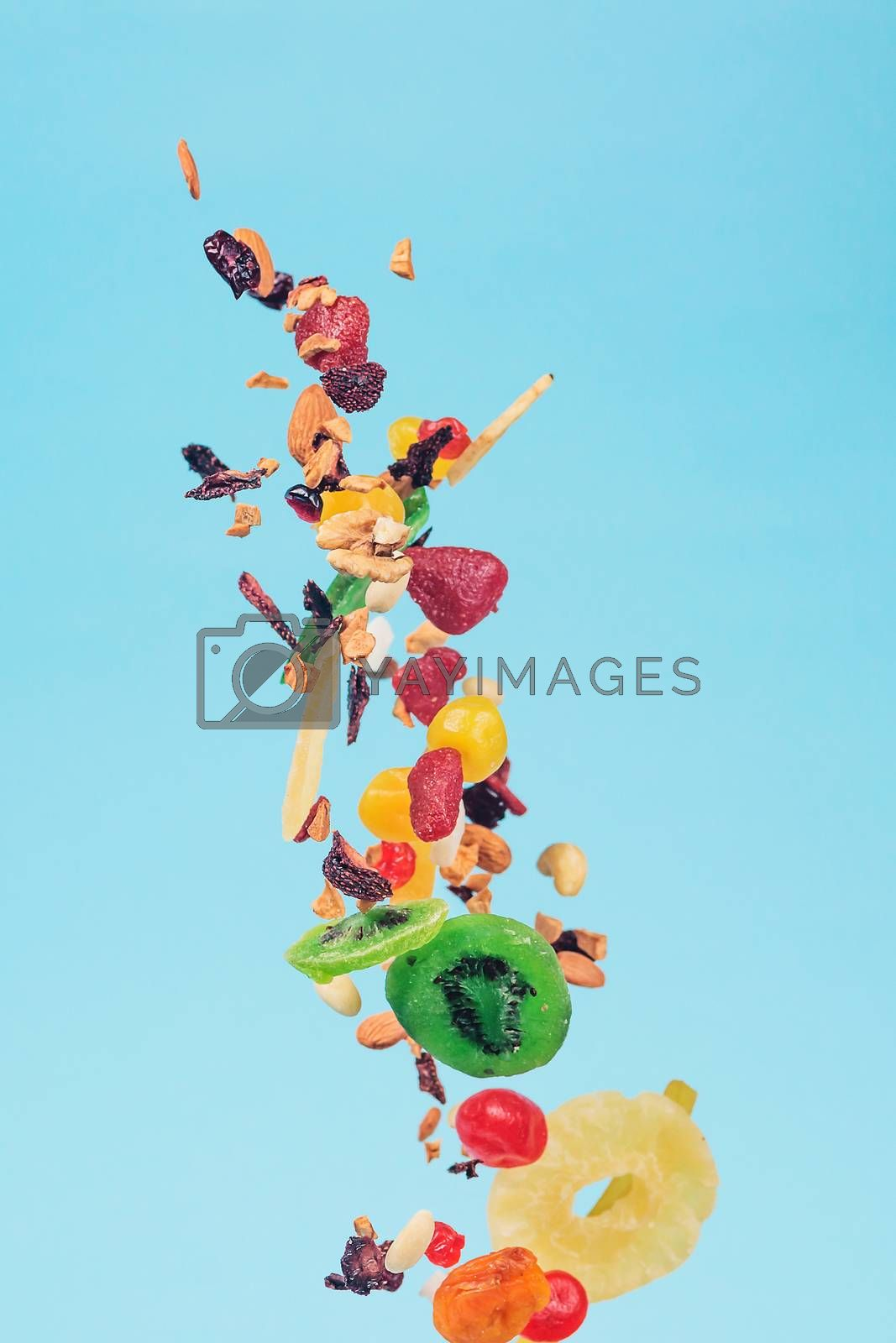 Dried and candied fruits and nuts flying on blue background. Stock photo of healty and nutrient food. Conceptual photo of vegan and vegetarian healty food.