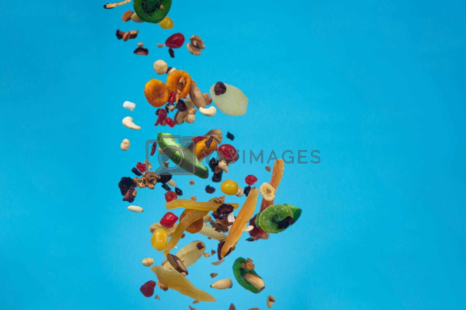 Dried and candied fruits and nuts flying on blue background. Sto by alexsdriver