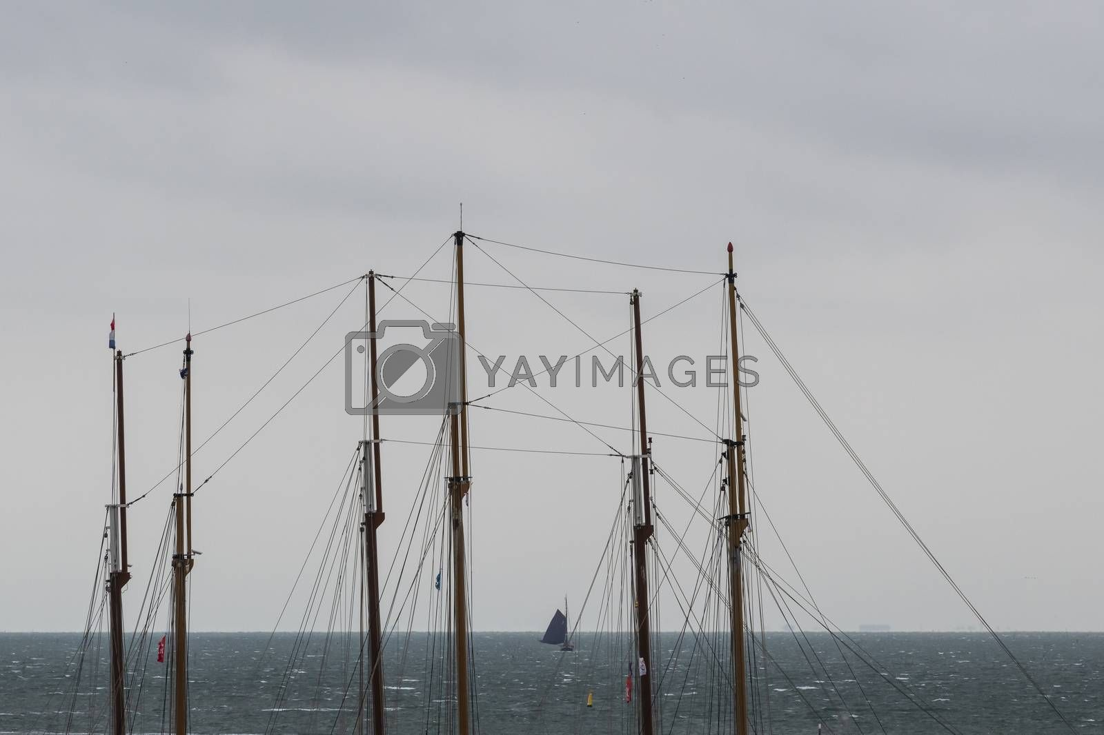 Sailboat at sea seen through the masts of two three-masted sailb by Tofotografie