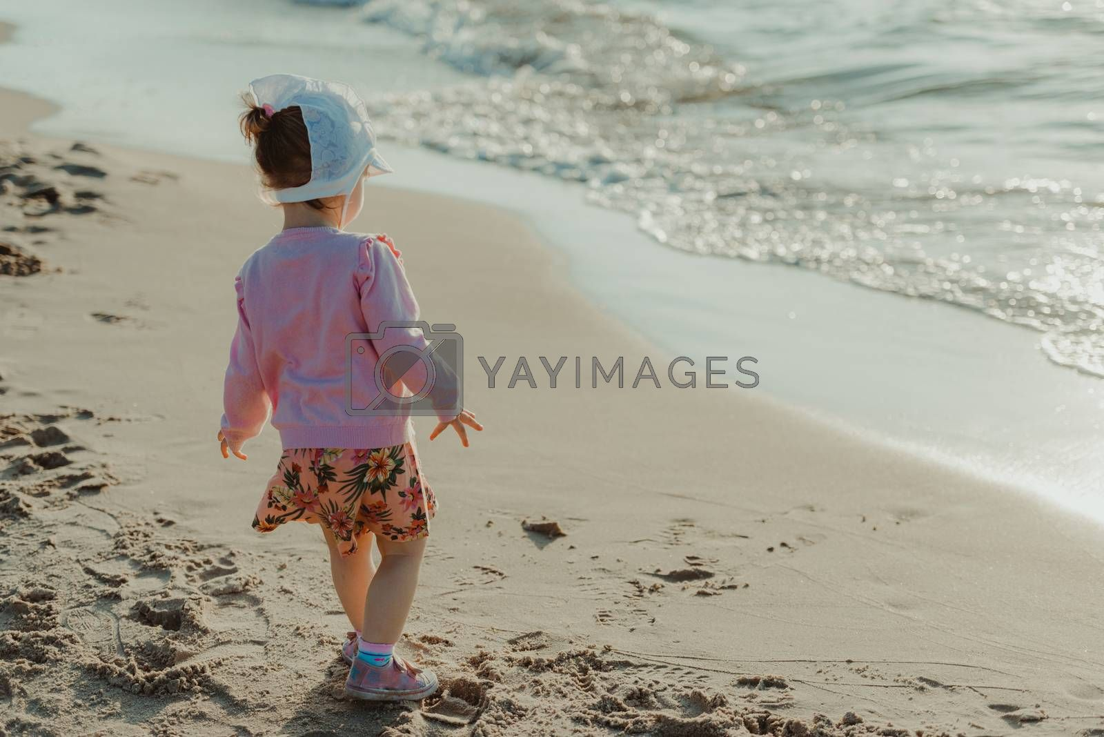 Adorable toddler girl on a sunny sand beach. Authentic childhood