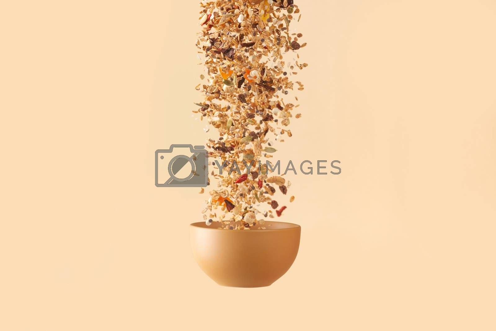 Falling granola with candied fruits and nuts  to baige flying bowl on baige background. Stock photo of nutritient food. Conceptual photo of vegan and vegetarian healthy food.