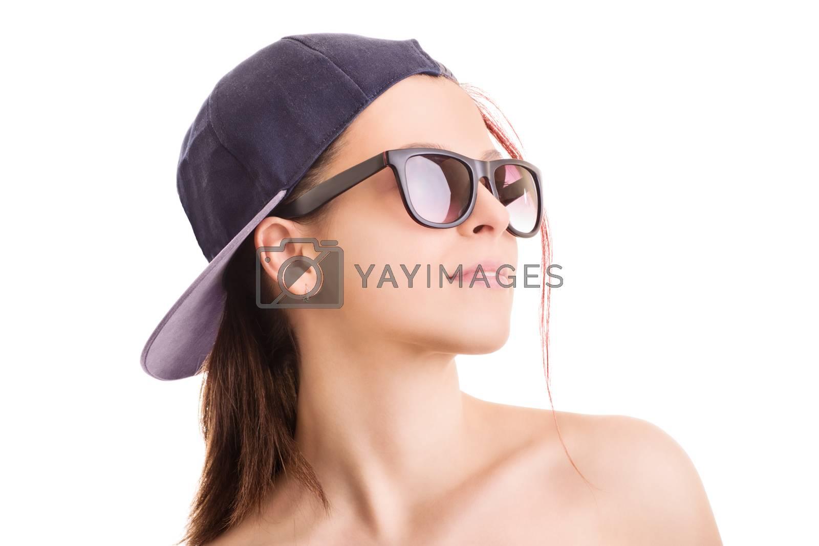 Profile shot of a beautiful stylish girl with backwards snapback cap and sunglasses, isolated on white background.