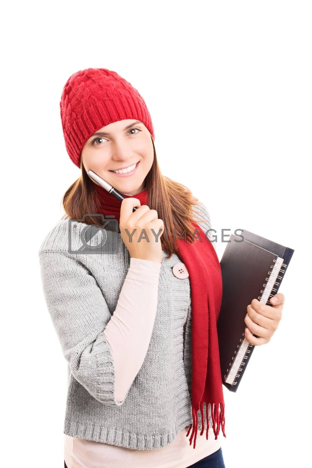 Portrait of a beautiful smiling female student in winter clothes holding a pen and notebooks, isolated on white background.