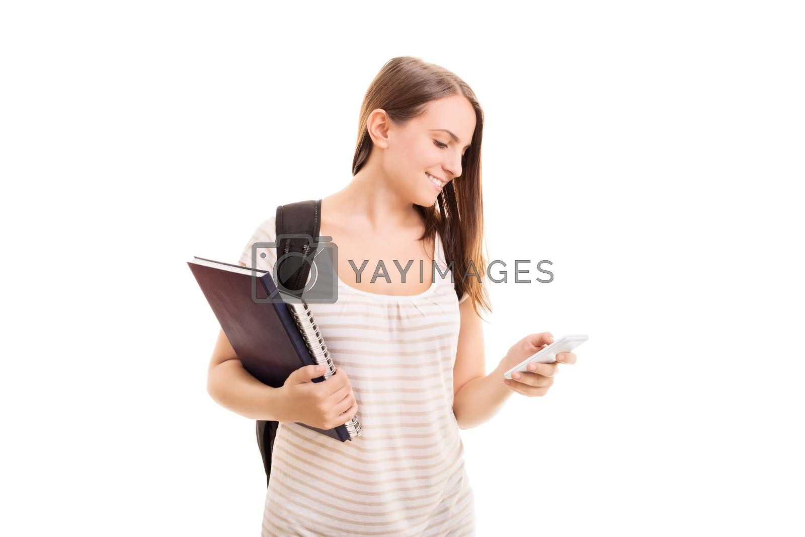 Beautiful young student girl with a backpack, holding notebooks, smiling and looking at her phone, isolated on white background.