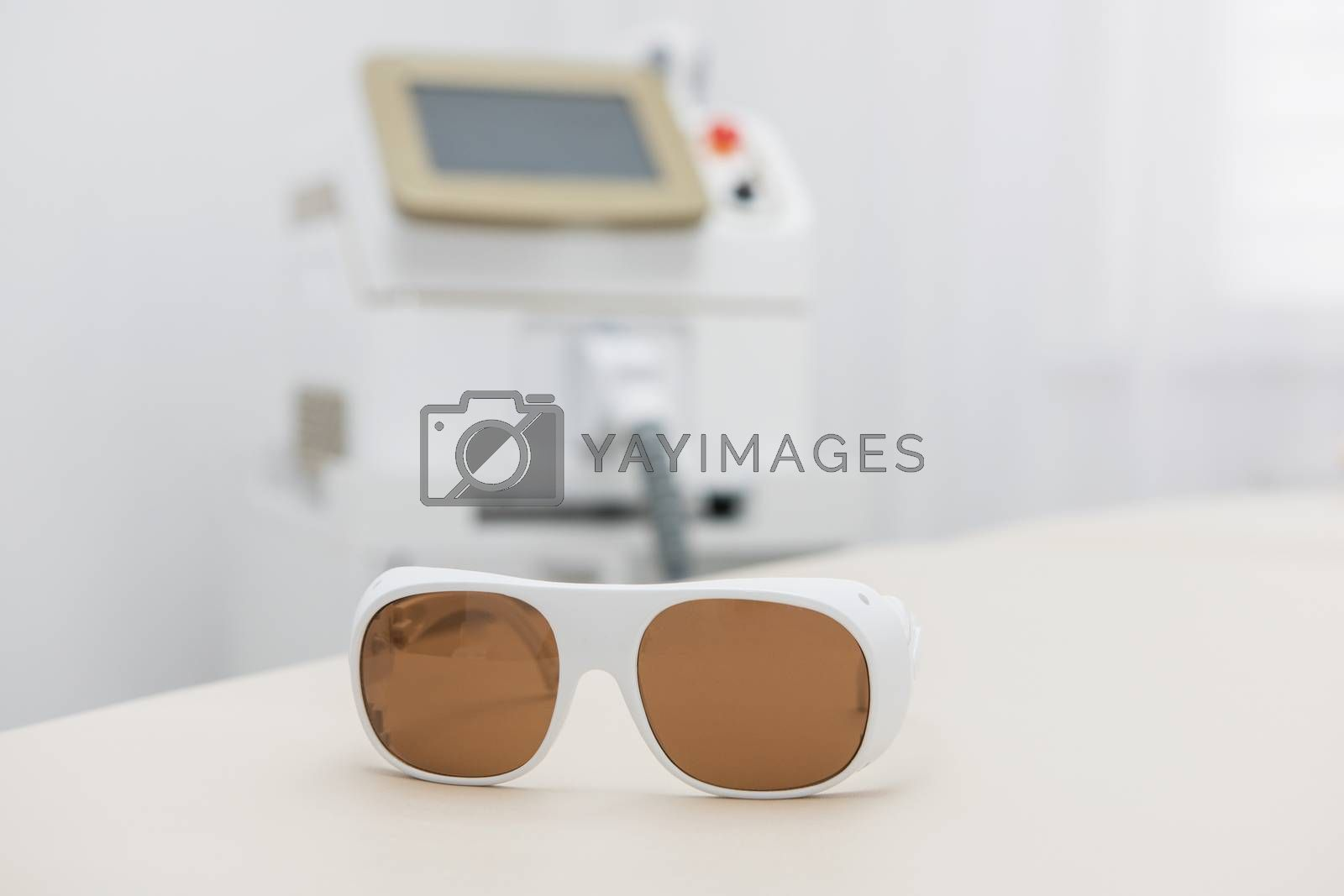 Protective glasses on laser epilation equipment in spa center. Hair removal cosmetology concept.