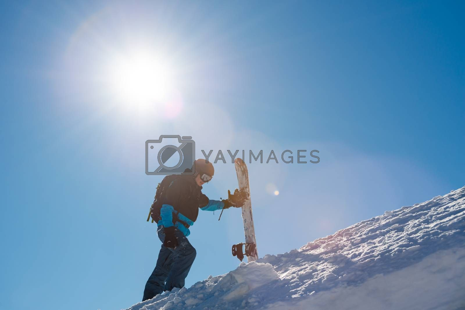 Snowboarder Climbing to the Top of the Slope with Red Snowboard in the Mountains at Sunny Day. Snowboarding and Winter Sports