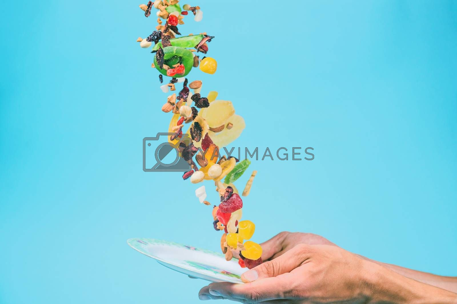 Male hands holding an empty white bowl on blue background. Candied fruits and nuts flying above the bowl. Stock photo of nutrient and healty food. Conceptual photo of vegan and vegetarial food and meal.