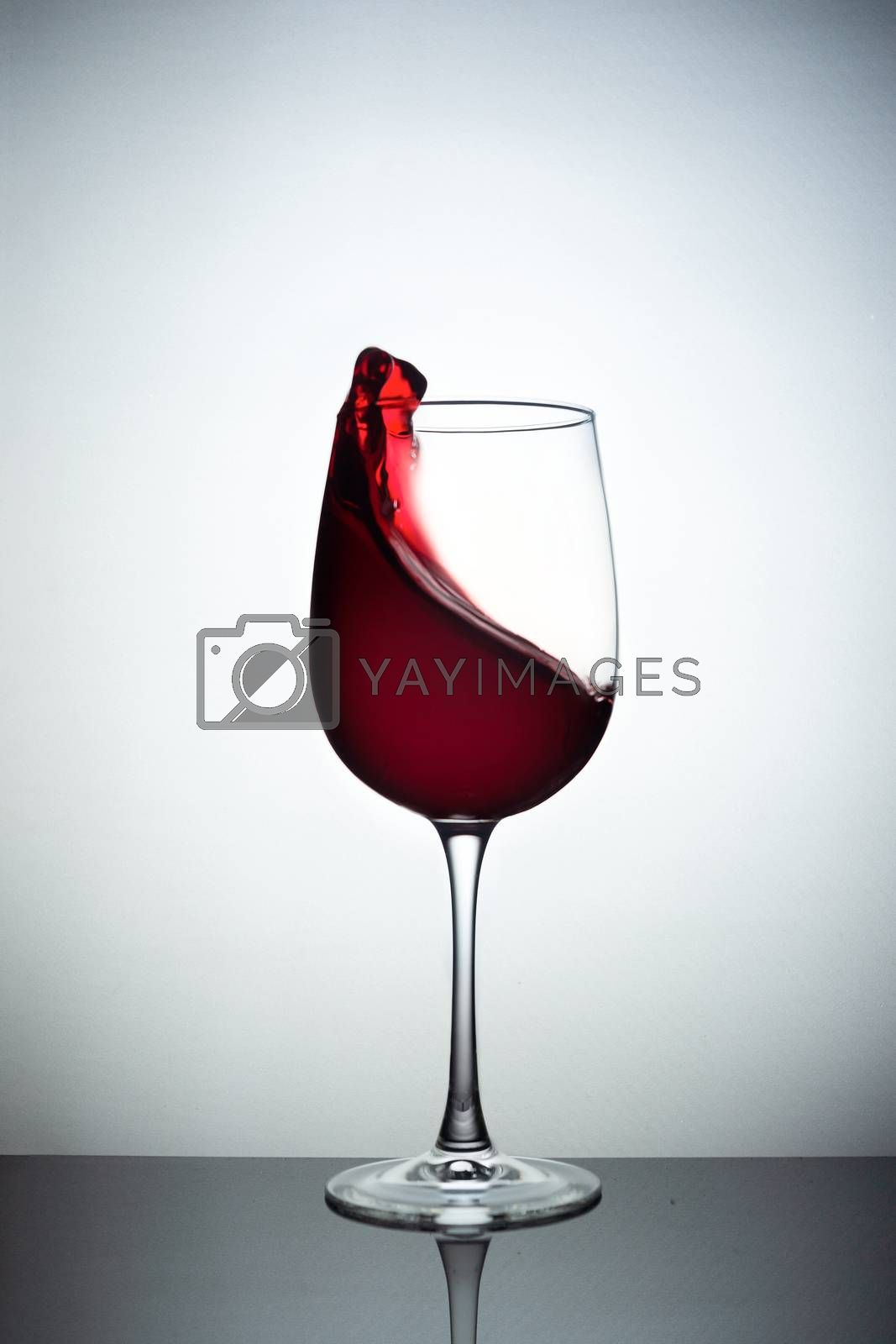 Creative photo of wine glass with storm in a glass on white background. A wine glass filled wine and a wave of wine flies from a wine glass. Wine glass stay on black glass sheet. Stock liquid motion photo.