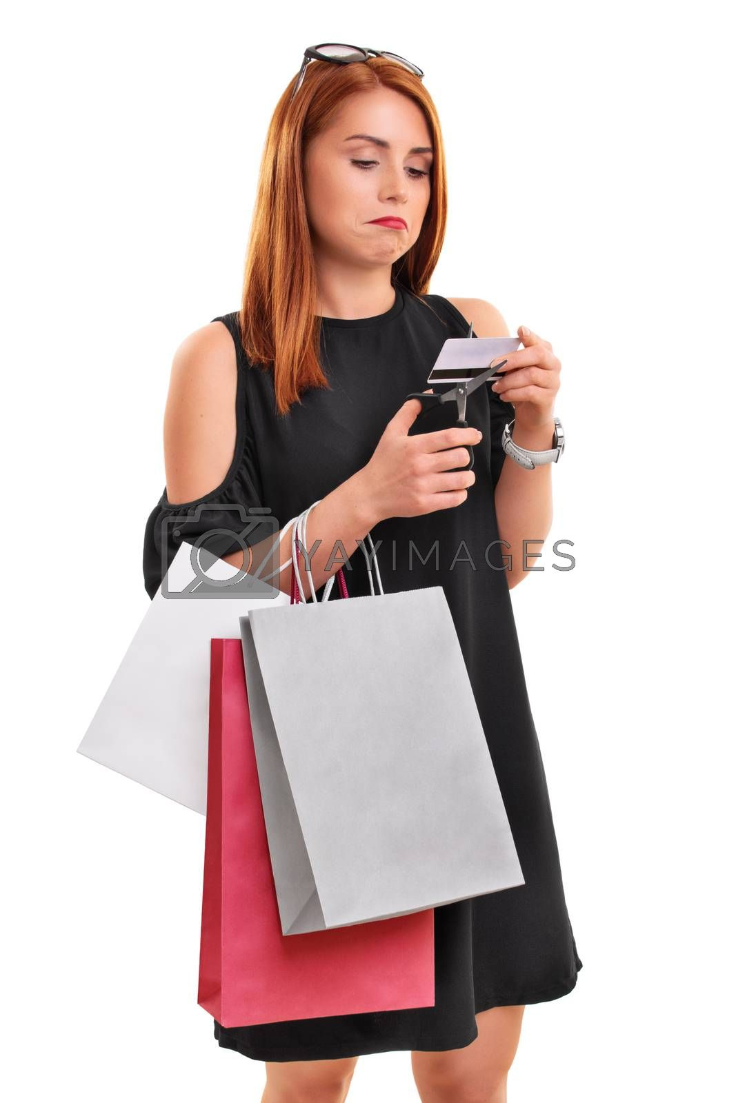 Portrait of a beautiful young girl in a stylish dress holing shopping bags cutting a credit card with scissors, isolated on a white background. Overspending concept. Financial debt concept.