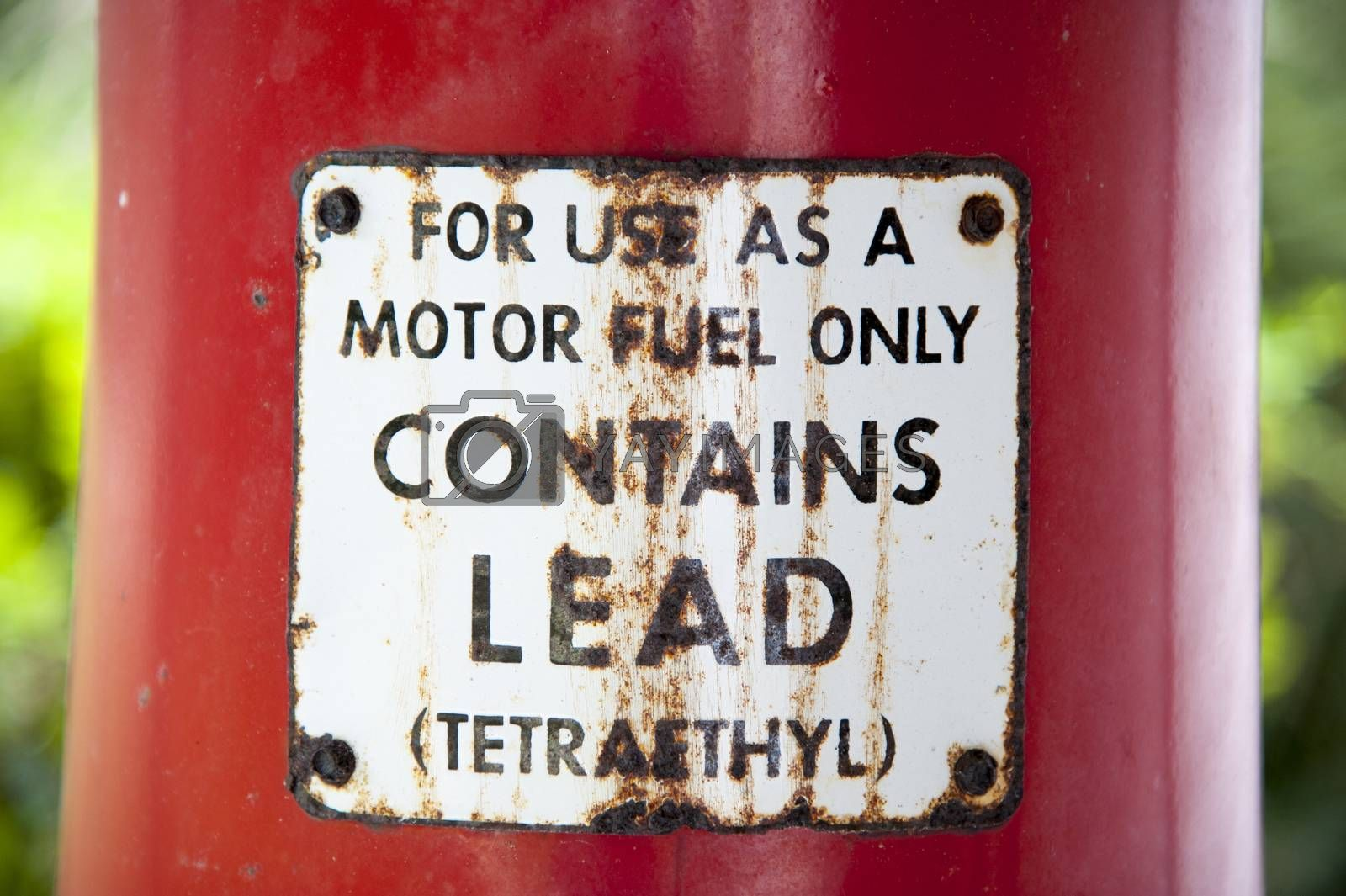 Old vintage rusty fuel pump sign on red pole