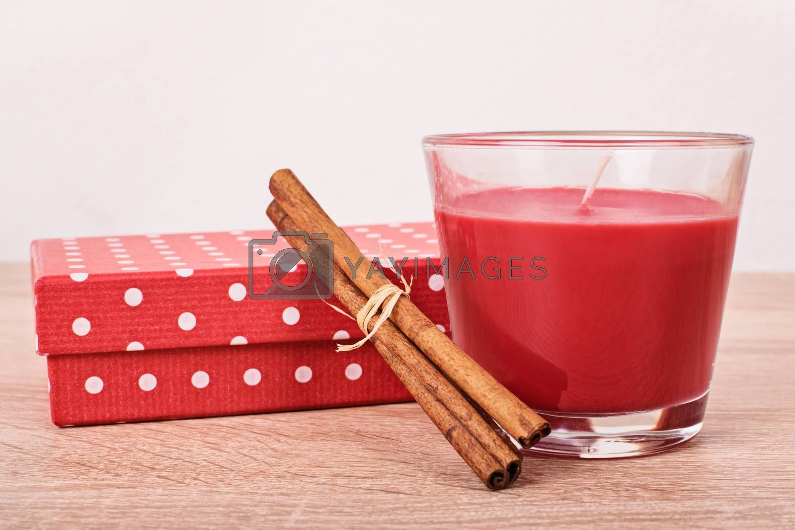 Close up shot of a gift box, aromatic red candle and cinnamon sticks on a wooded table.