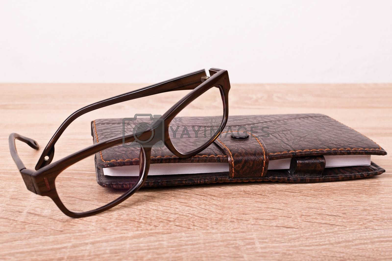 Close up of a planner notebook and glasses placed on a wooden table.
