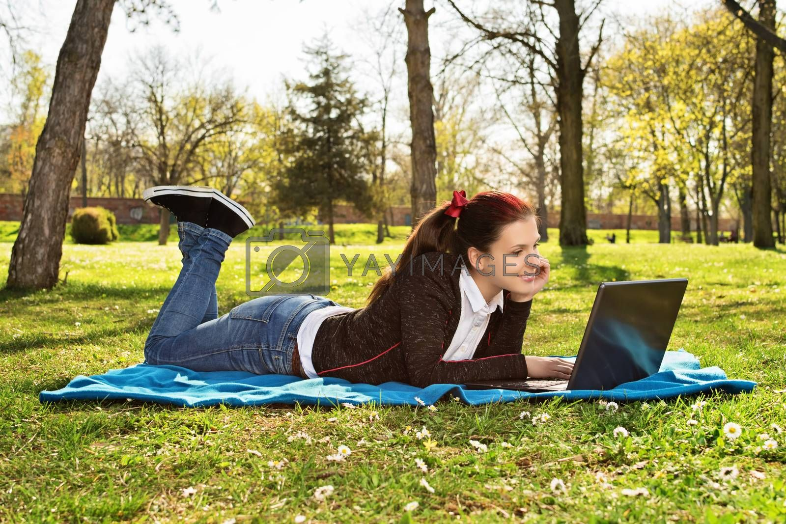 Beautiful casual student girl with laptop outdoors. Smiling woman lying on a blanket on the grass with computer, surfing on the Internet or preparing for exams. Technology, education and remote working concept.