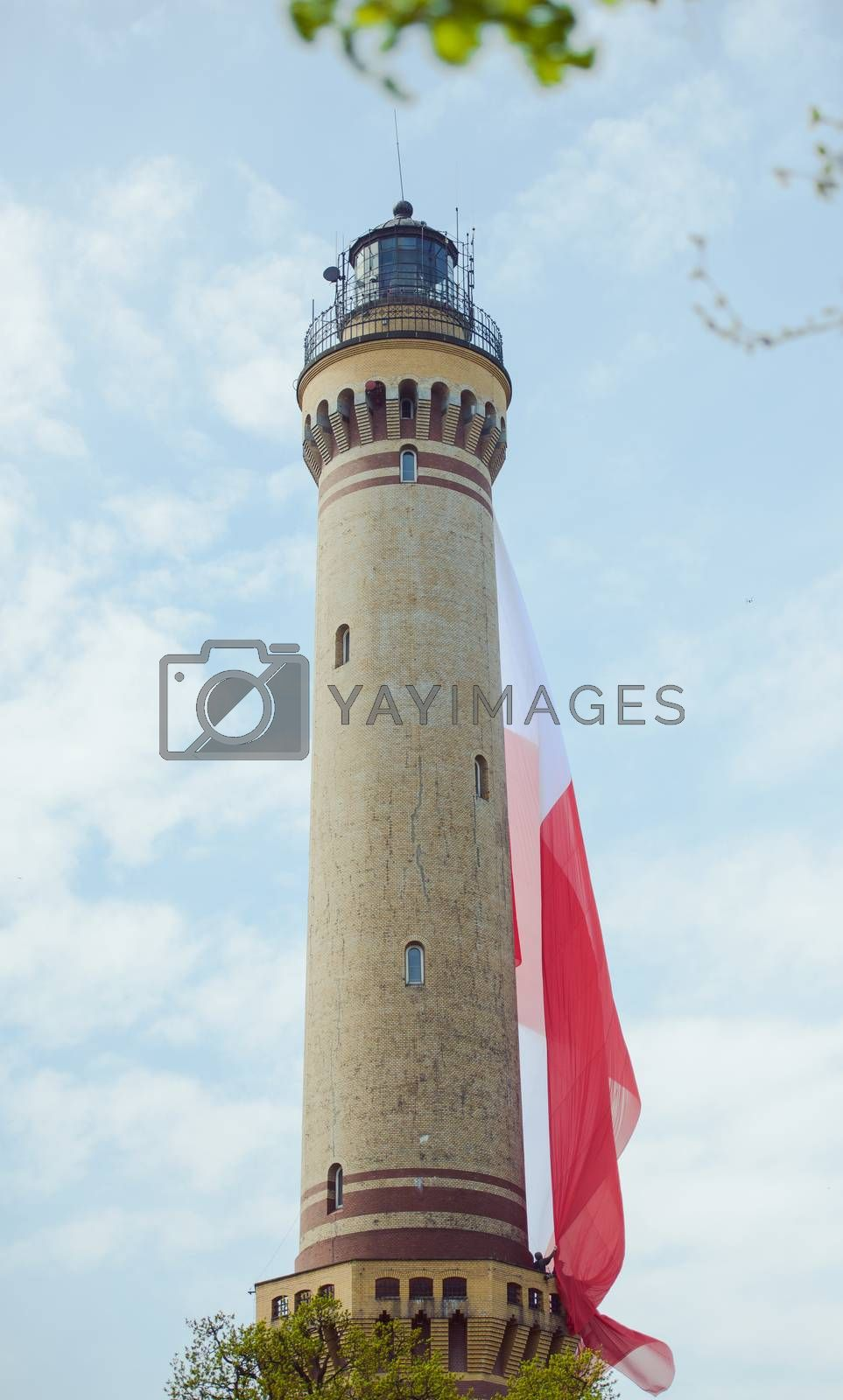 Polish flag hung on at historical lighthouse located in Swinoujscie, Poland, The construction was build in 1828 and height is 65 meters. 19th century. Top tallest Lighthouse in the World