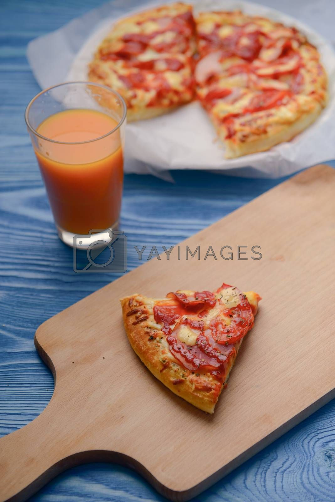 Homemade pepperoni pizza on the table. Tomato, cheese and ham main ingredients.