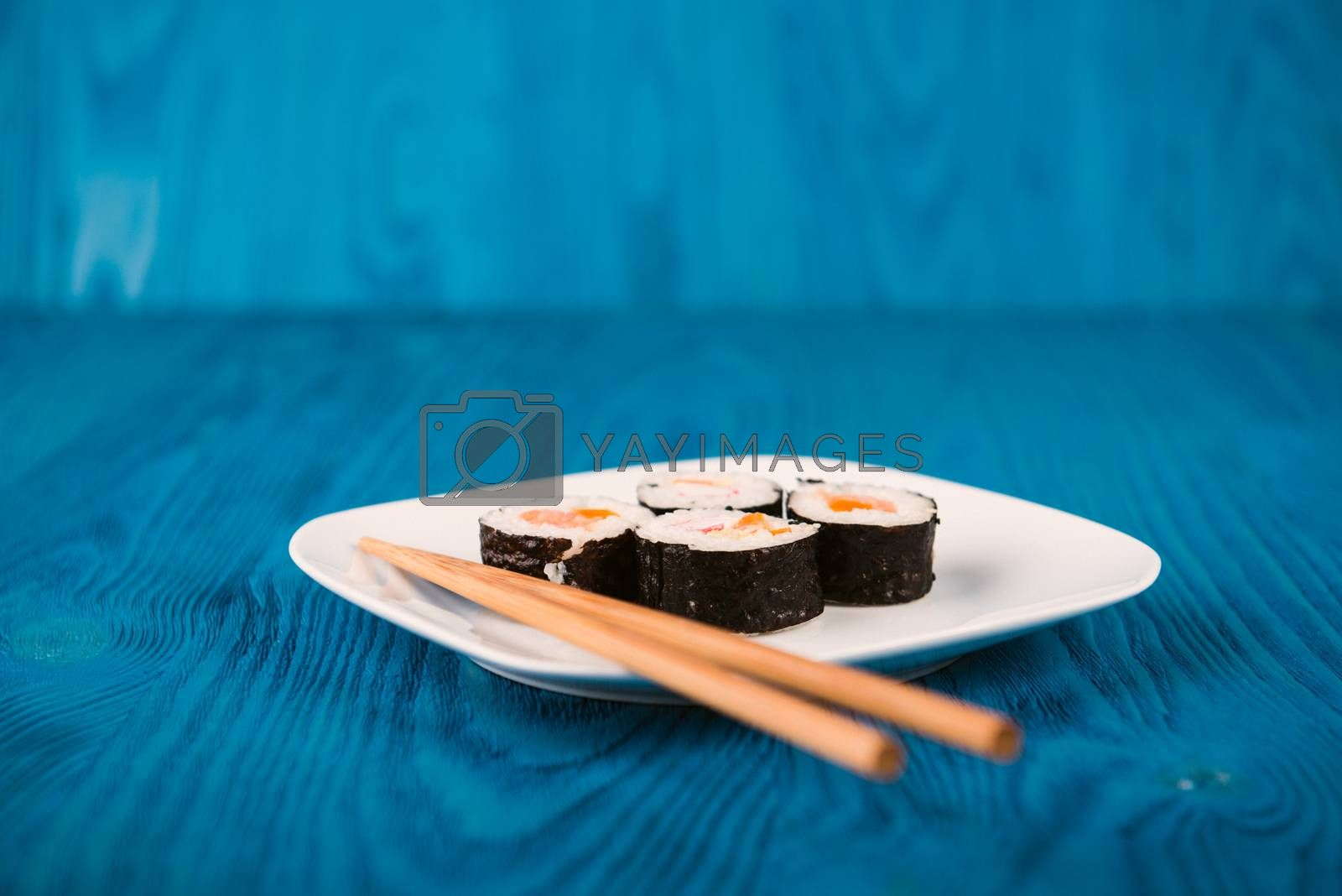 Appetizing tasty Japan rolls on a plate isolated on blue wooden background