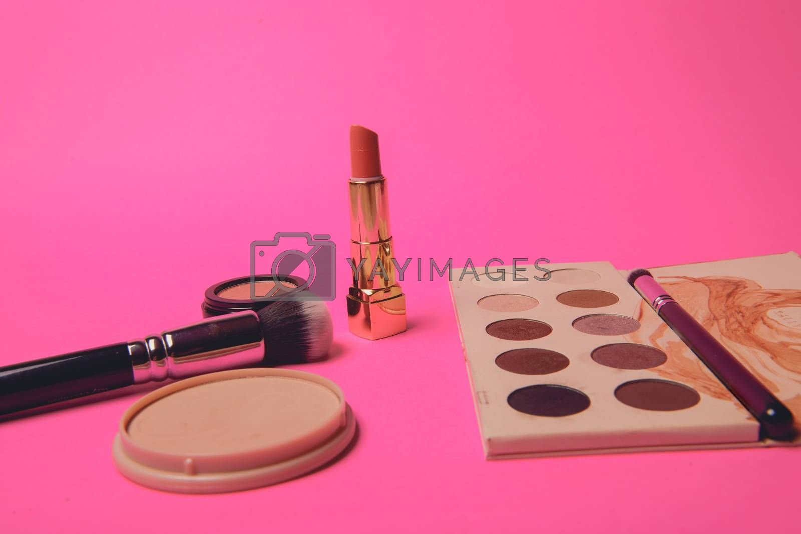 Palette of colorful eye shadows. Pink background.