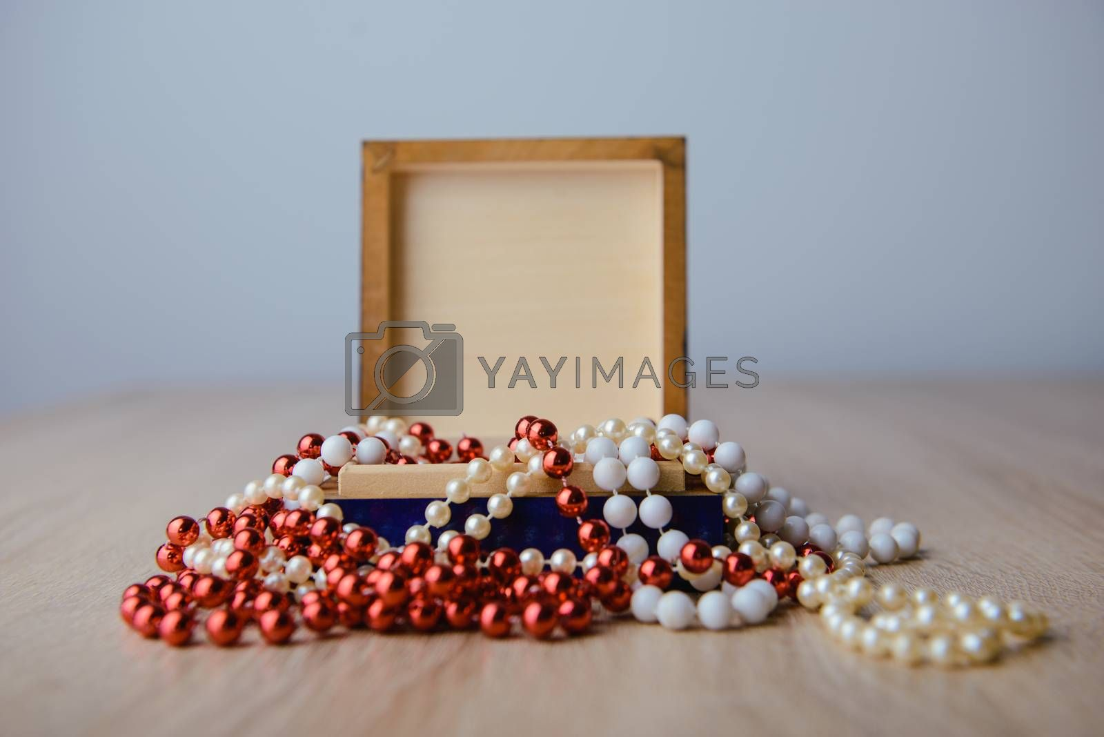 A photograph of gift box and red beads necklace on wooden background
