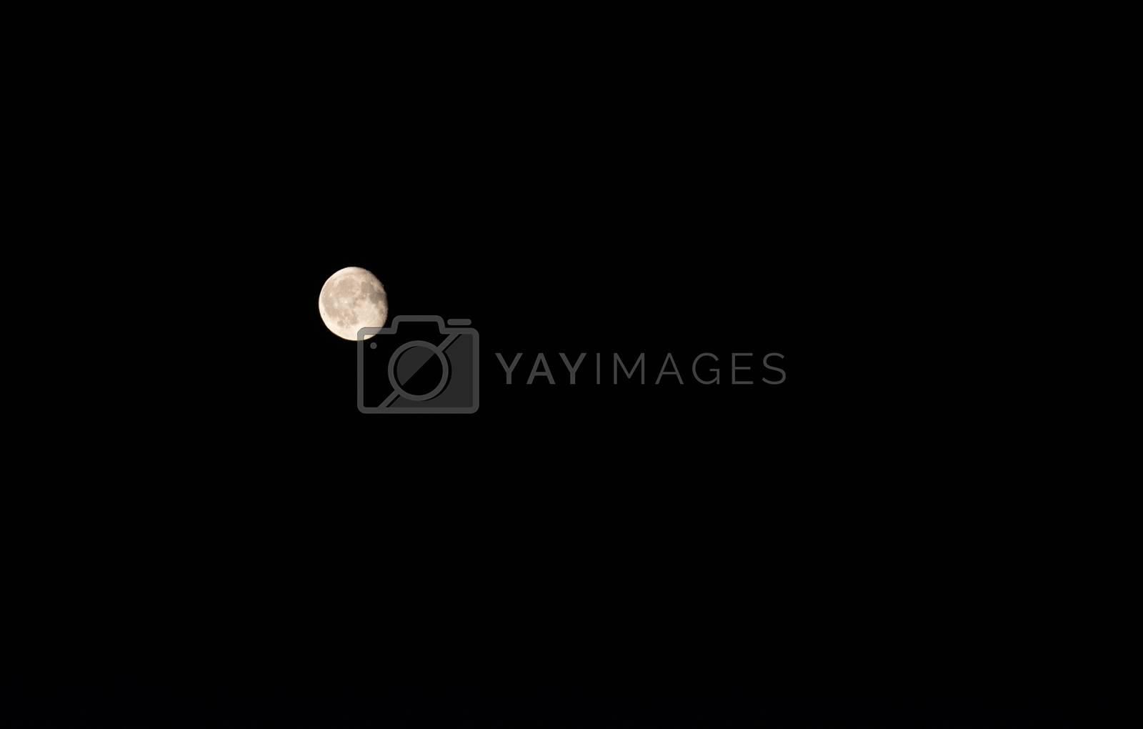Full moon over dark black sky at night.
