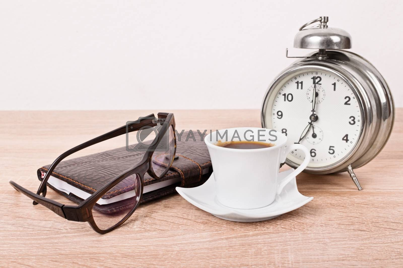 Close up of a leather covered planner notebook, glasses, alarm clock and a cup of coffee placed on a wooden table.