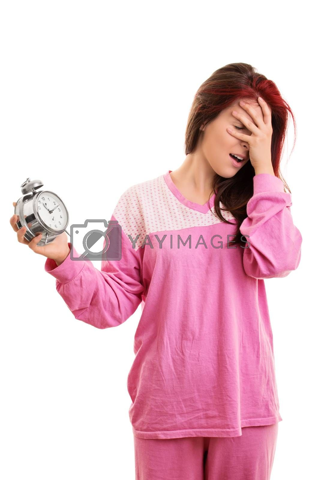 Being late concept. Portrait of a young woman in pink pajamas holding an alarm clock and covering her face with her hand, looking tired and annoyed, isolated on white background. Girl panicking about being late.