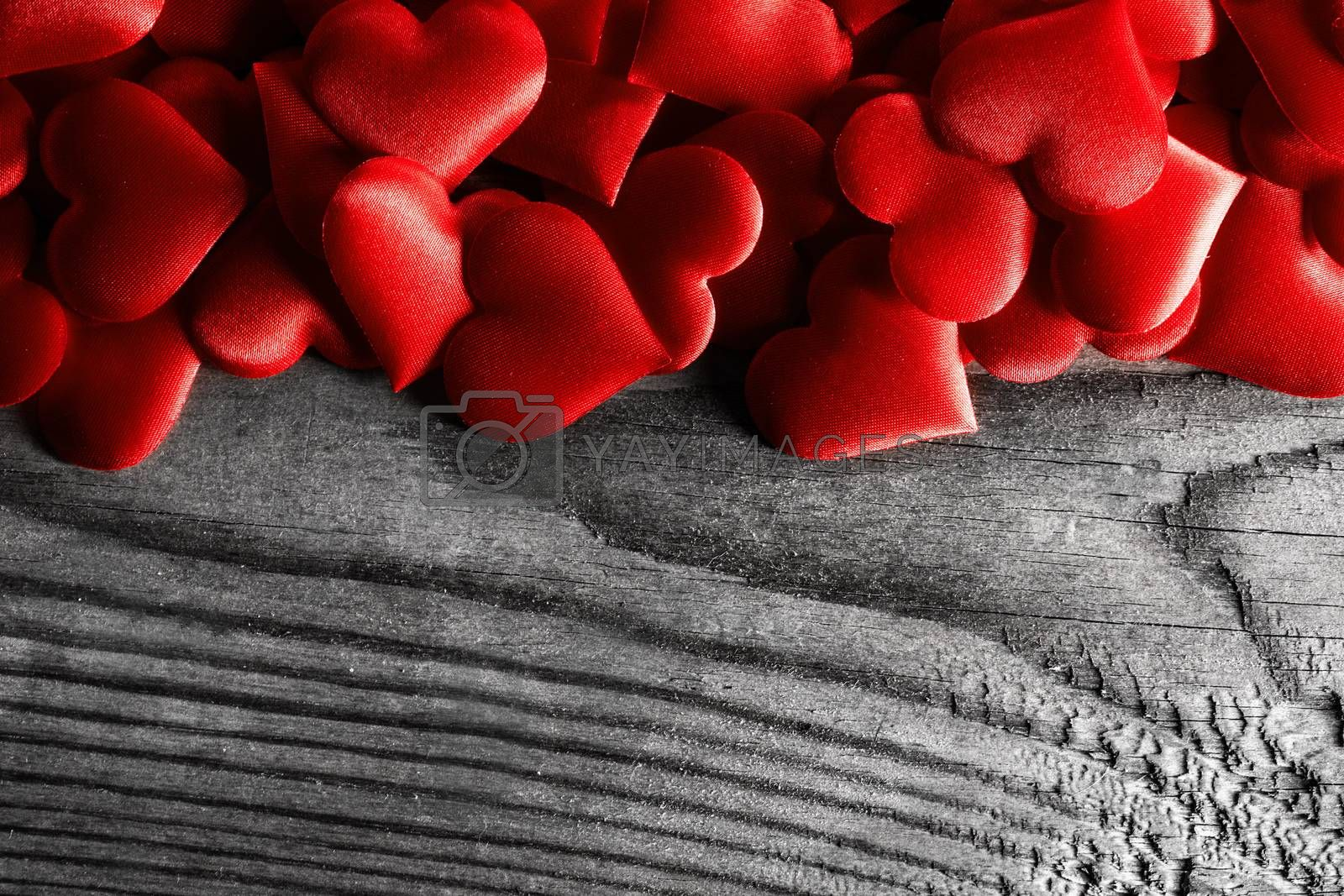 Valentine's day many red silk hearts on wooden background, love concept