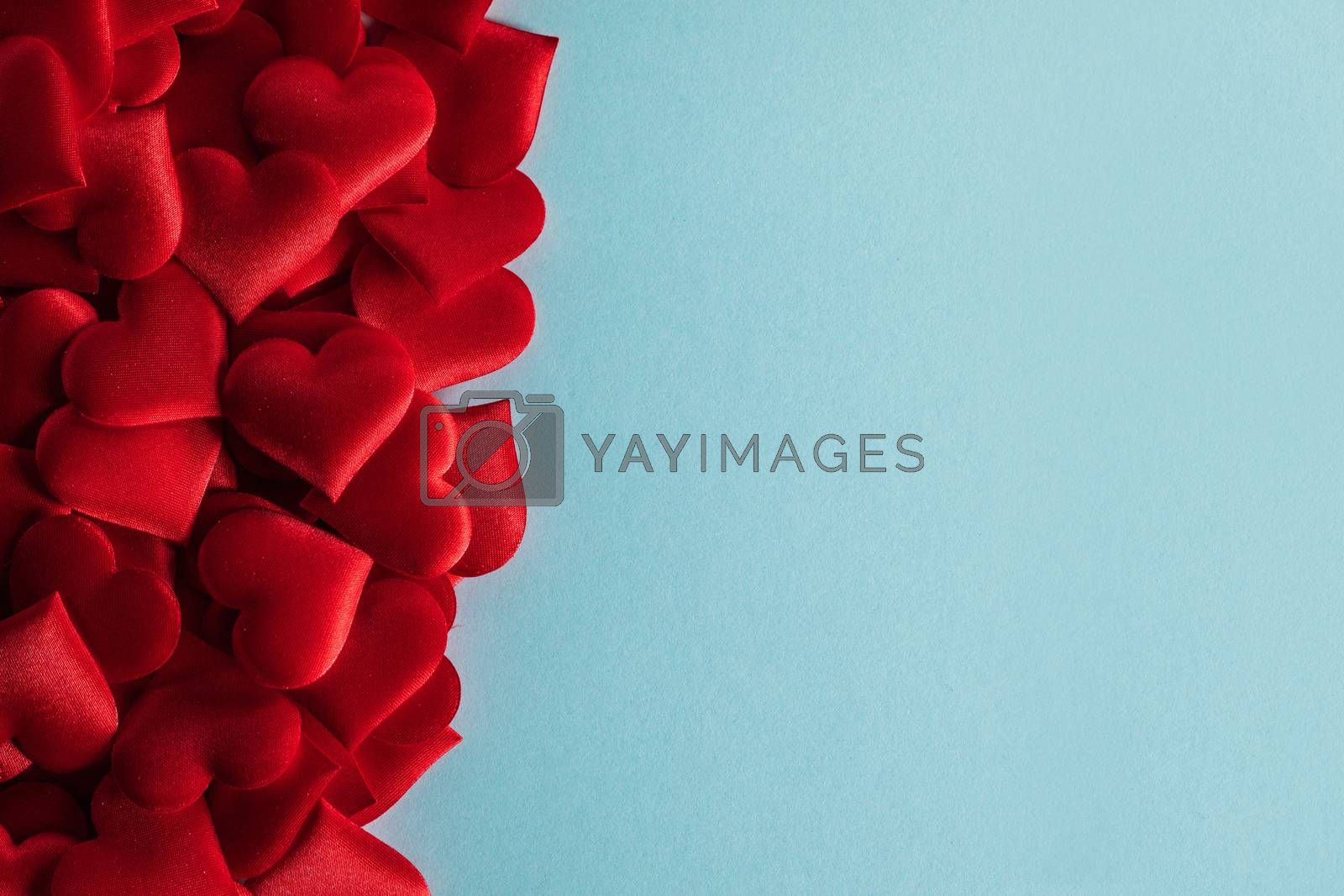 Valentine's day many red silk hearts on blue paper background , border frame on red with copy space, love concept