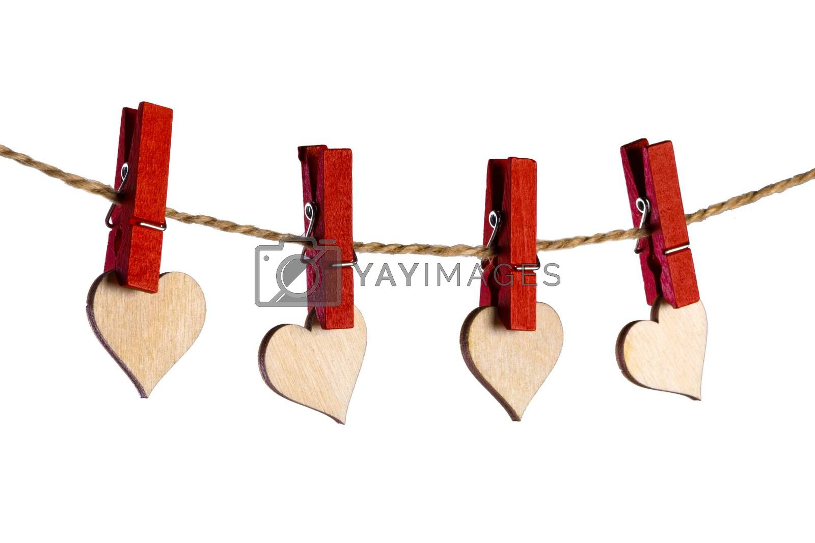 Red clothes pegs and wooden hearts on rope isolated on white background. Valentines day concept