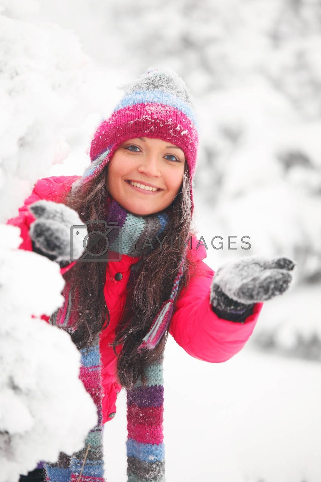 Young cheerful woman play snowballs in winter park