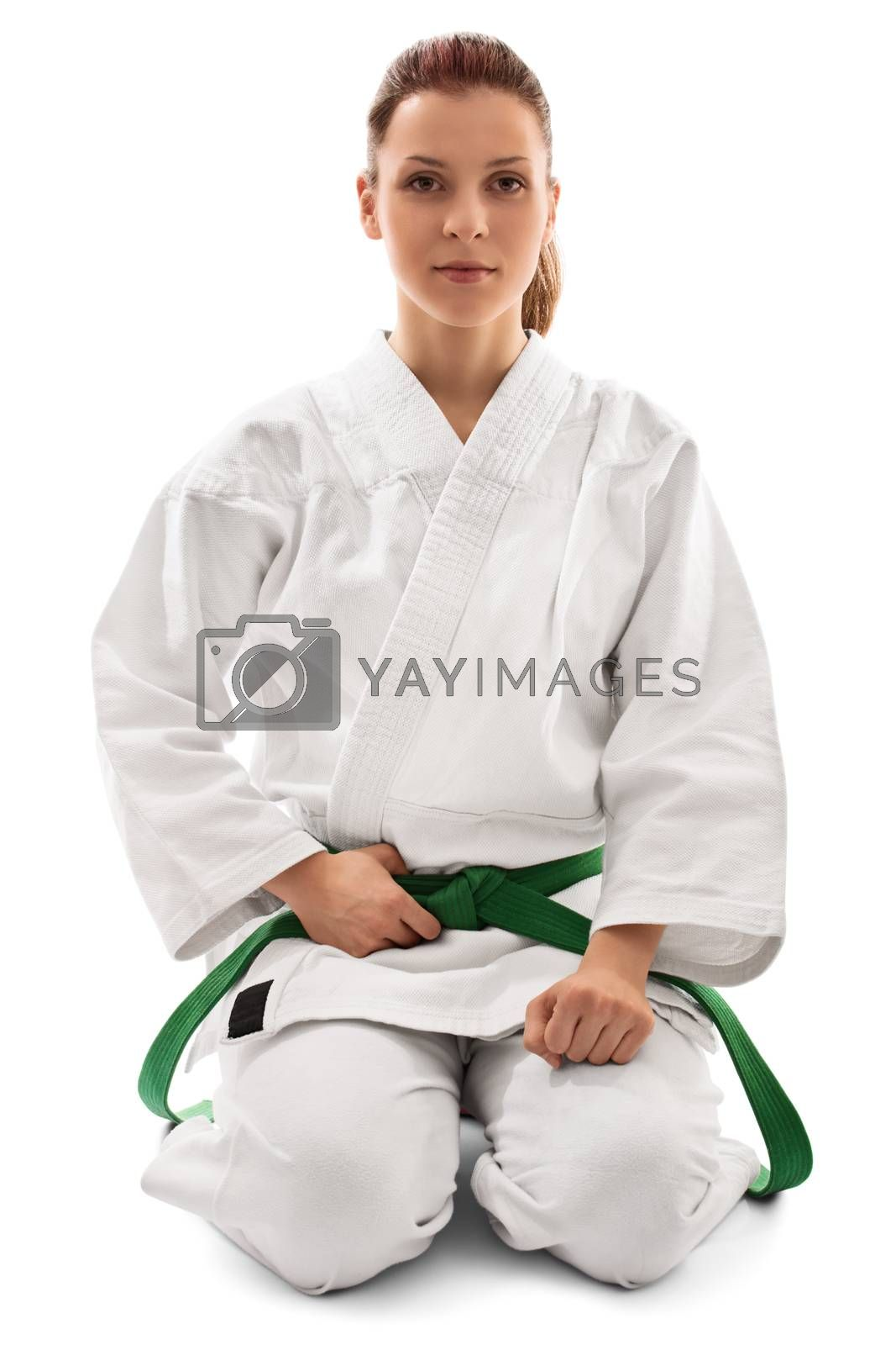 Portrait of a beautiful female martial arts fighter in a white kimono with green belt in the seiza position, isolated on white background. Calm young girl in a kimono kneeling down.