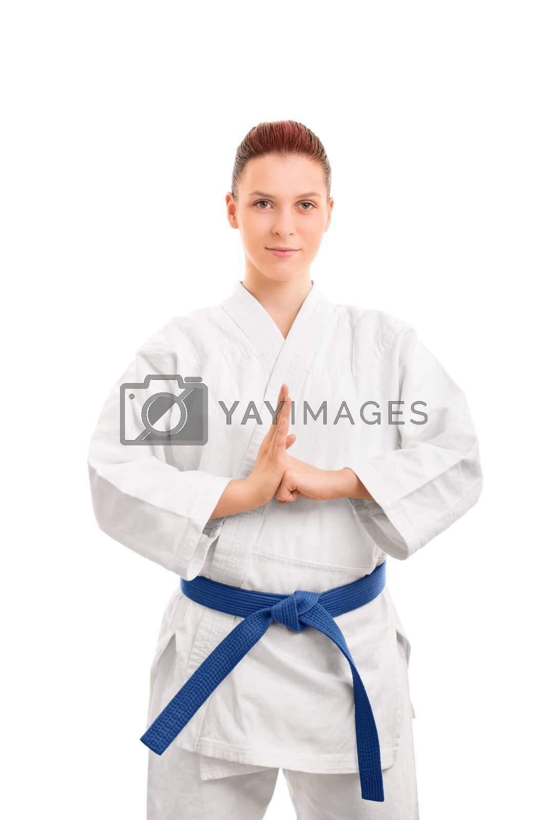 Portrait of a beautiful female martial arts fighter in a white kimono with blue belt performing a hand salute, isolated on white background. Girl in a kimono performing a hand salute.