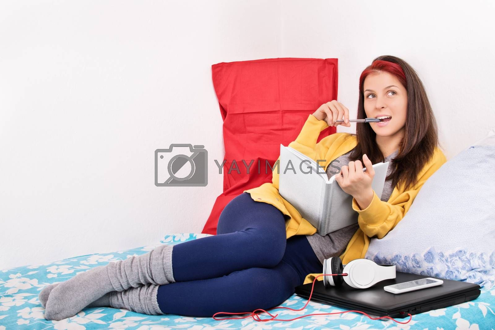 Beautiful young girl in her room holding a notebook, biting a pen, thinking, wondering, while sitting in bed next to laptop and headphones. Girl writing in her diary.