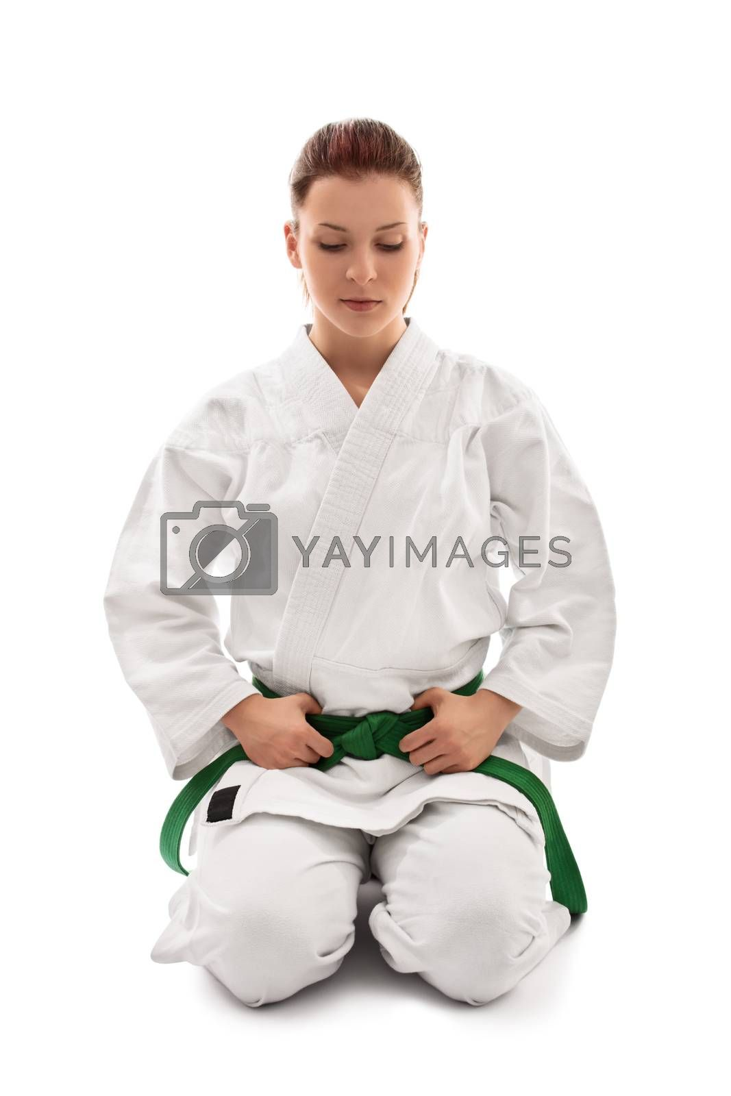 Beautiful female martial arts fighter in a white kimono with green belt in the seiza position looking down, isolated on white background. Calm young girl in a kimono meditating.