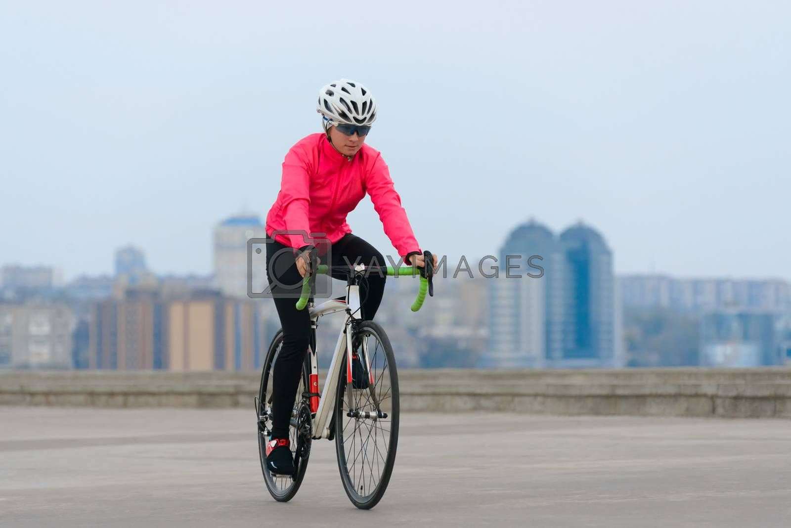 Young Woman Cyclist Riding Road Bike on the Street in the City at Cold Autumn Day. Healthy Lifestyle and Urban Sport Concept.