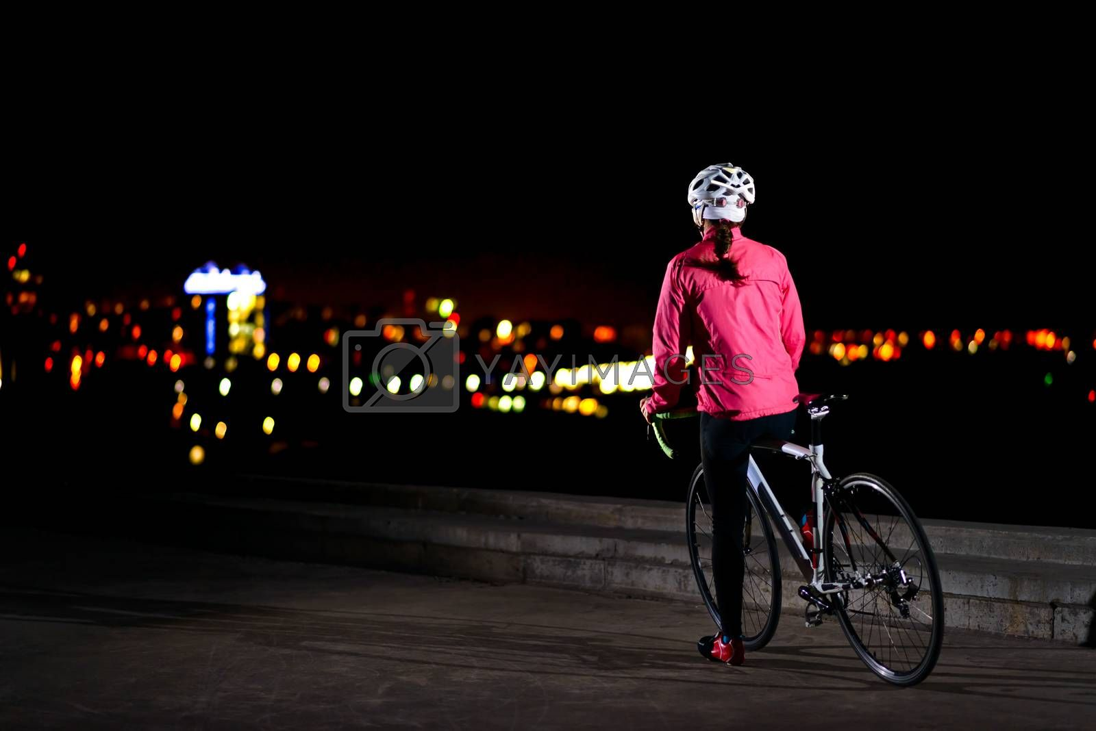 Young Woman Cyclist Resting with Road Bike and Looking at Night City Lights at Cold Autumn. Healthy Lifestyle and Urban Sport Concept.