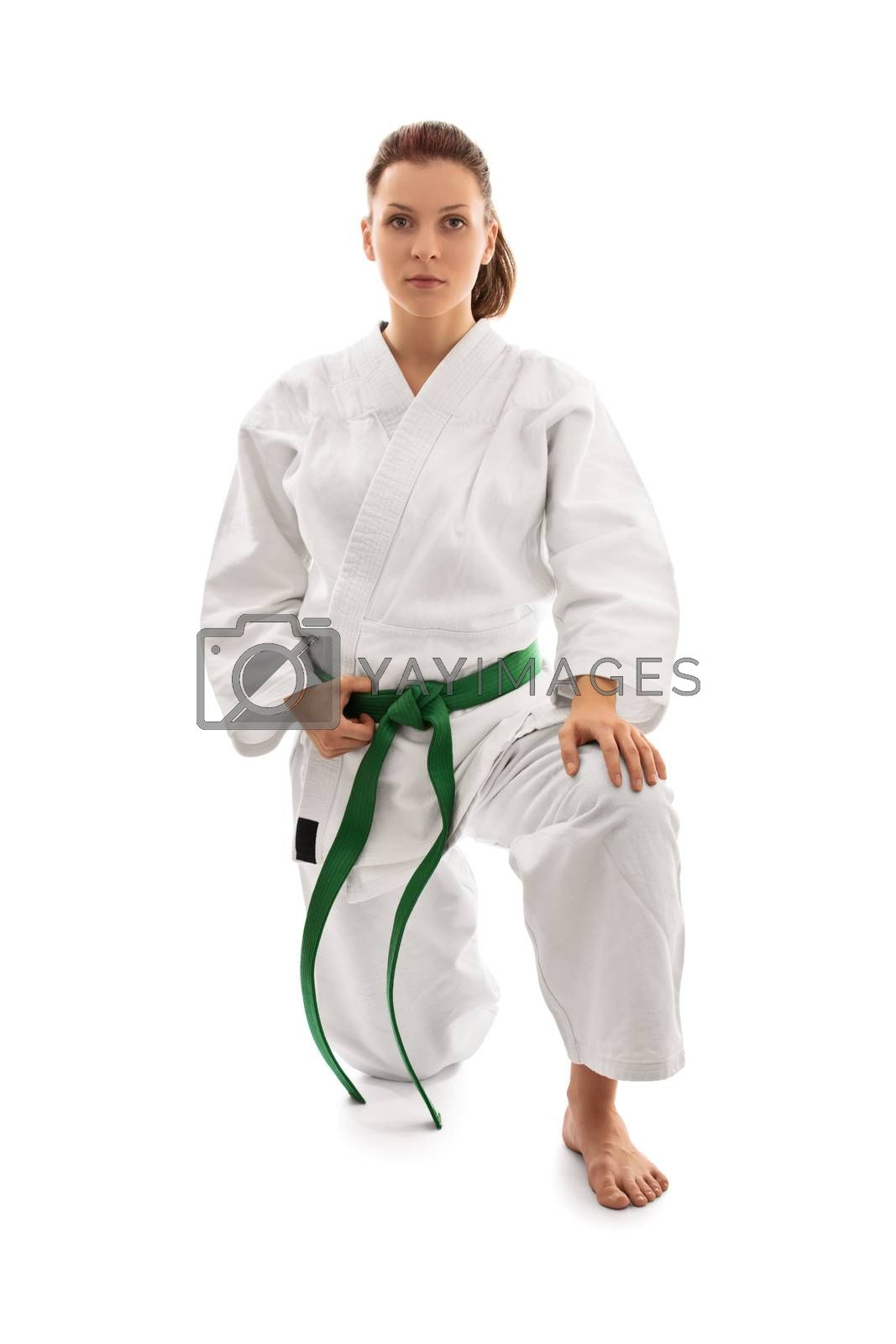 Young female martial arts fighter in white kimono and green belt kneeling on one knee and looking serious, isolated on white background. Body and spirit bent to my will.