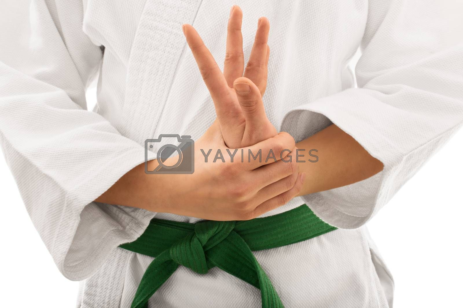 Close up shot of the mid section of a martial arts fighter in white kimono with green belt stretching and twisting her hand, isolated on white background.