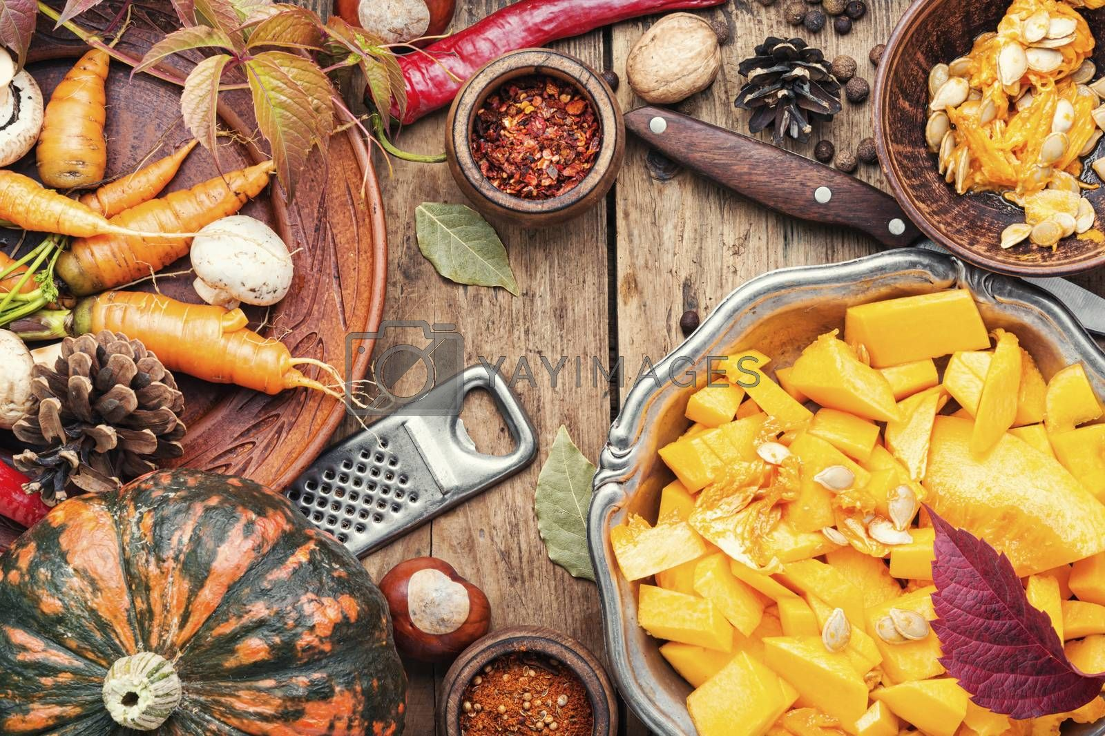 Pumpkin cut in a pieces and food ingredients.Autumn vegetarian food on wooden background