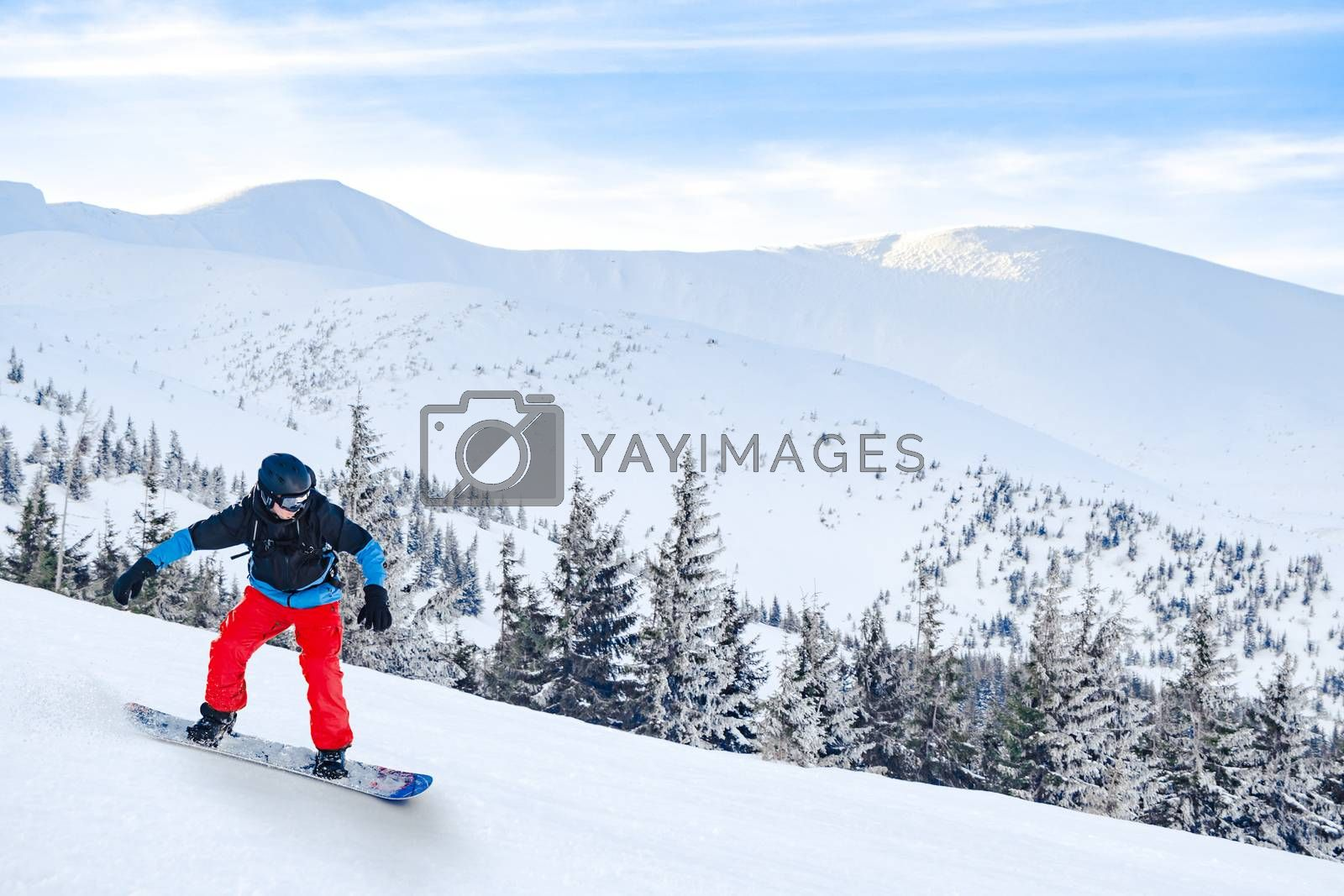 Snowboarder in Red Riding Snowboard in the Beautiful Mountains. Snowboarding and Winter Sports Concept.