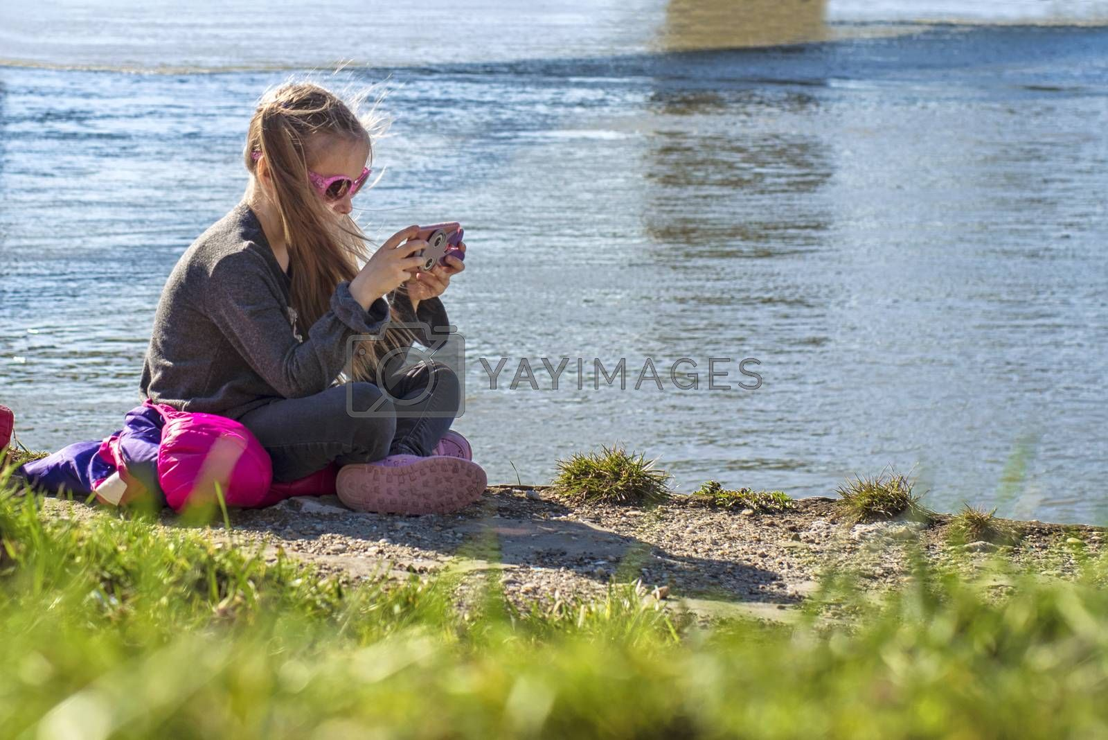 A little girl is sitting on the bank of the river with a telephone.