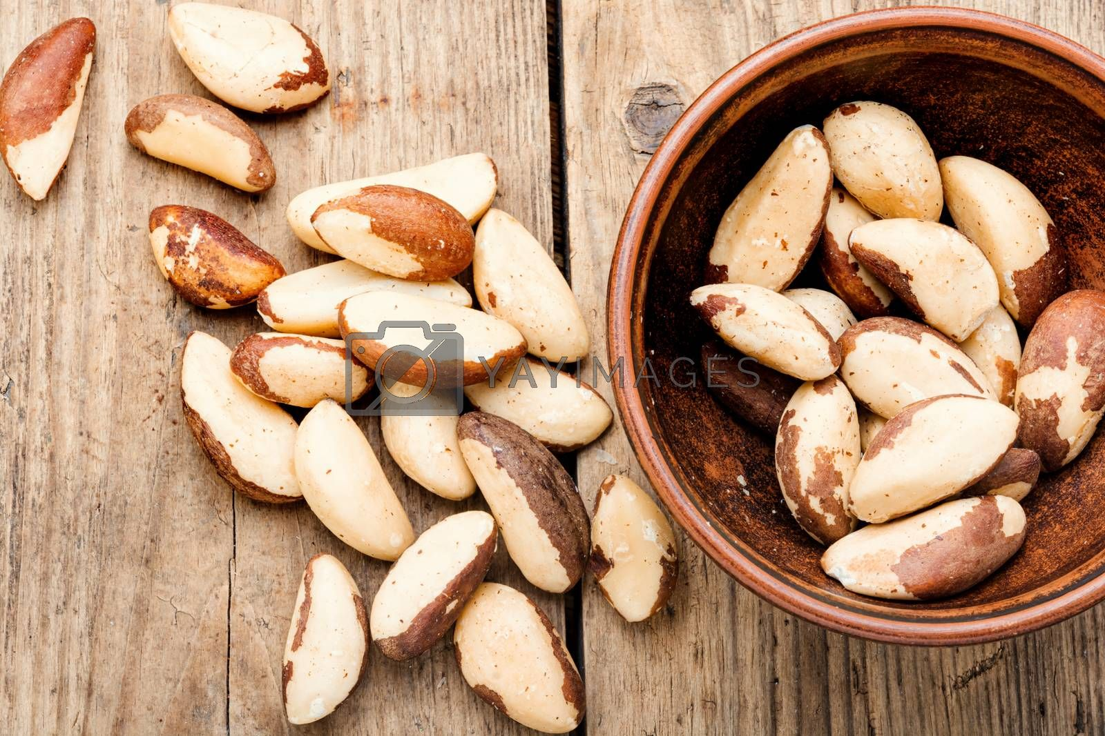 Tasty peeled brazil nut in bowl on old wooden table