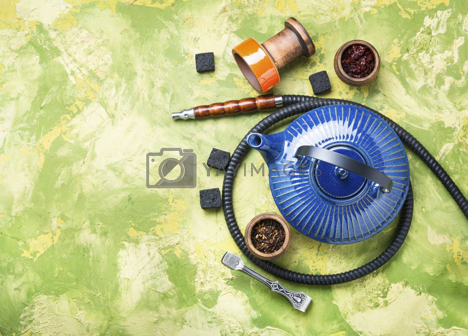Details of tobacco hookah and teapot with tea.Eastern smoking shisha.Space for text