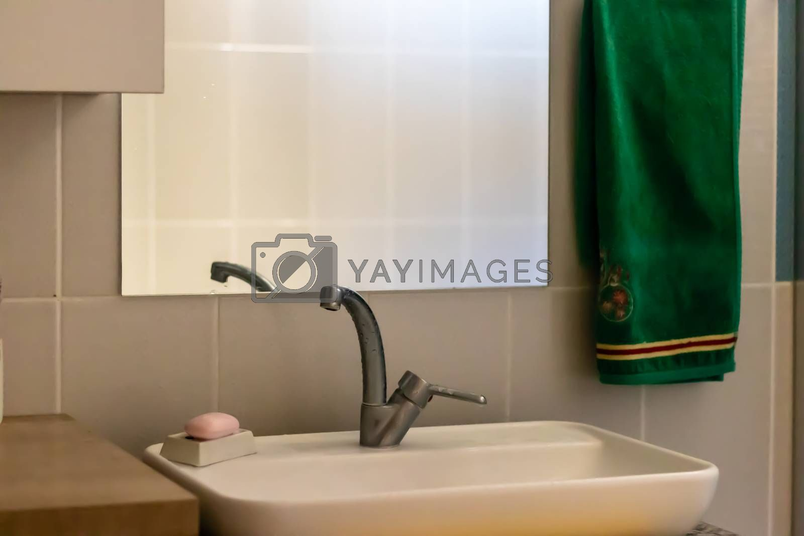 an interior shoot from a modern bathroom - there is sink and green towel. photo has taken at izmir/turkey.