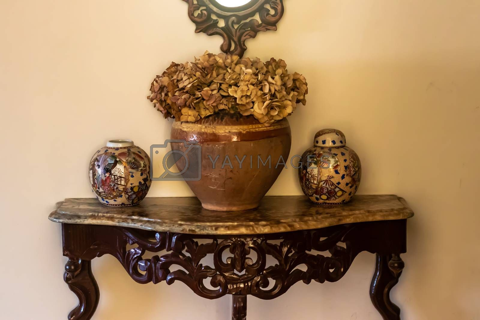 yellow color dominated good composed shoot from some antique items. there is some vases, containers and table.