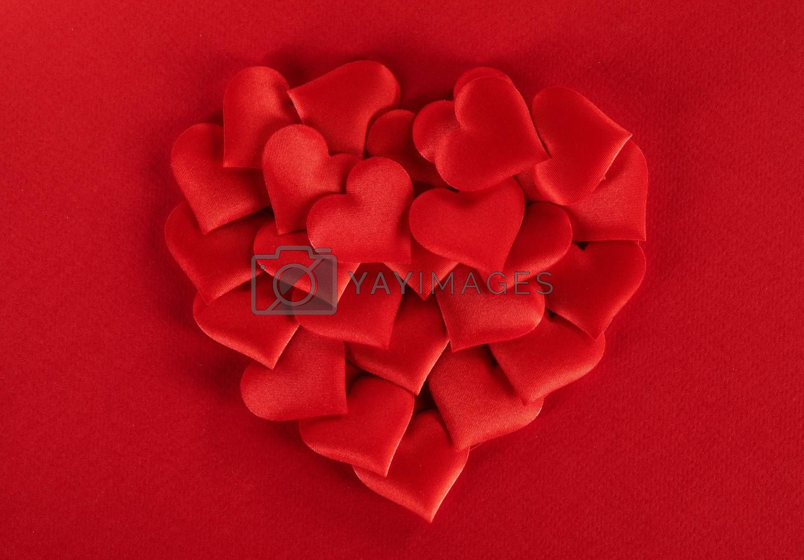 Valentine's day many red silk hearts ob paper background, love concept