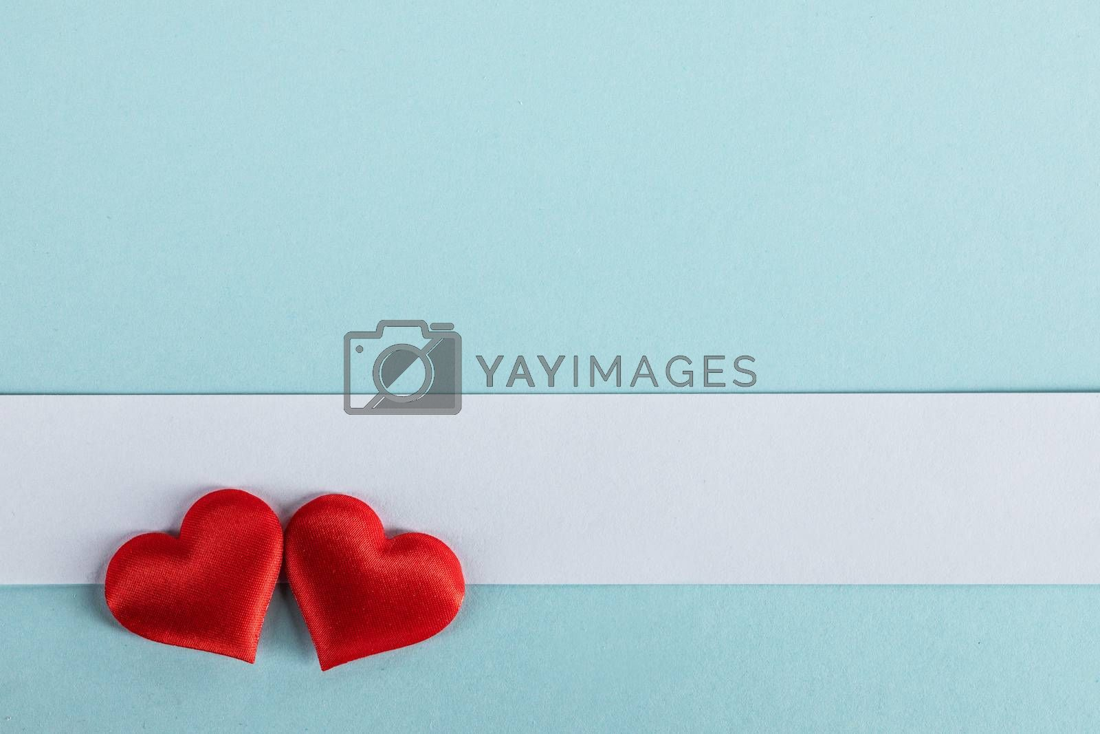 Valentine's day two red silk hearts and white paper on blue paper background, love concept