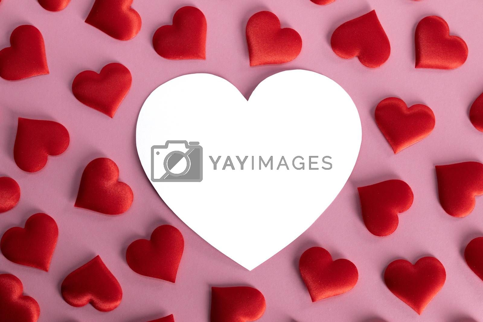 Valentine's day many red silk hearts and white heart shaped card on pink background, love concept